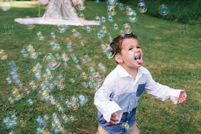 Boy catching bubbles on tongue
