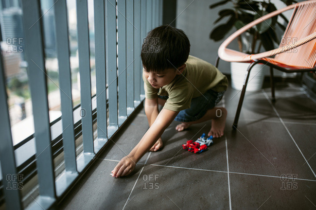 Boy playing with toys by window