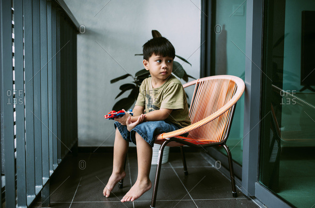 Boy sitting in chair playing with toys