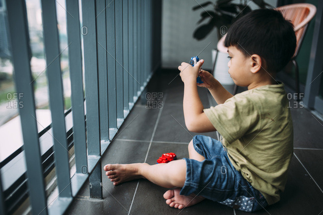 Young boy sitting on floor playing with toys by window