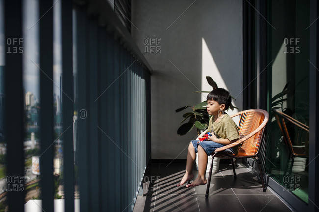 Boy sitting in chair with toys looking out window