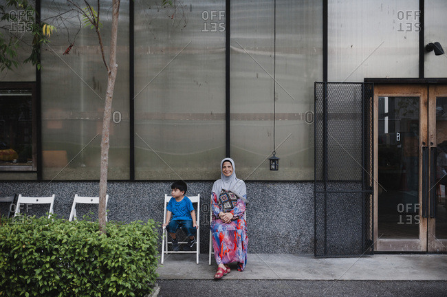 Boy and grandmother sitting outside building in Kuala Lumpur, Malaysia