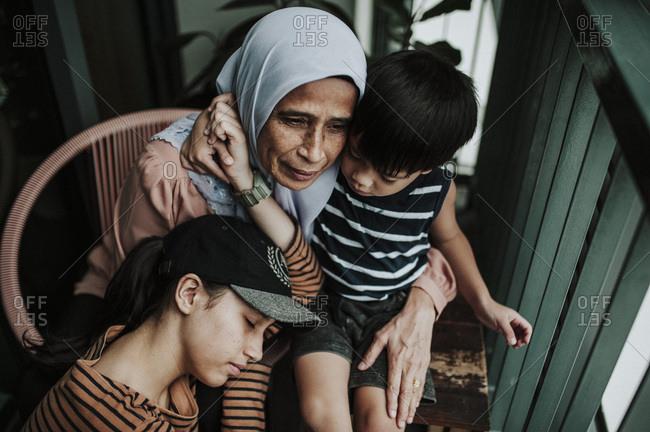Grandmother hugging her grandchildren