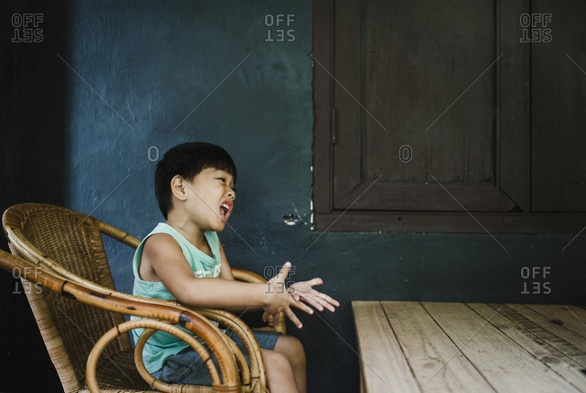 Little boy sitting in wicker chair making silly faces