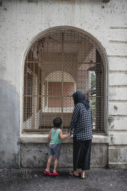 Mother and son looking into building window in Kuala Lumpur, Malaysia