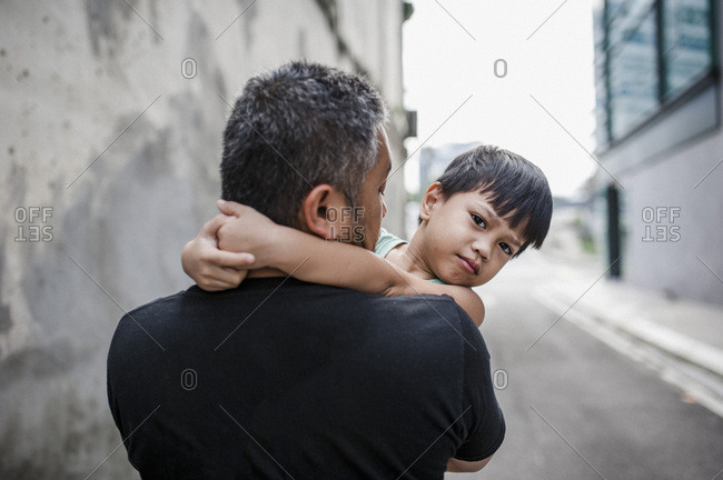 Boy looking over father's shoulder while walking down street