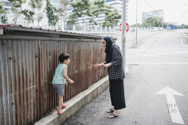 Mother and son playing while on a street in Kuala Lumpur, Malaysia