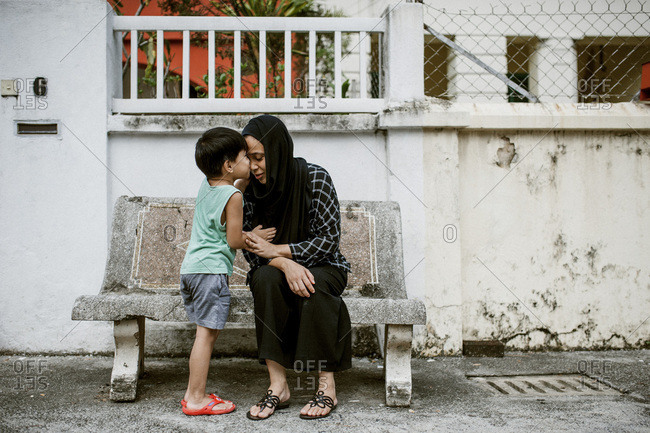 Son giving mother a kiss on a bench in Kuala Lumpur, Malaysia