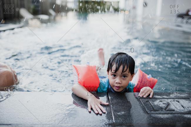 Little boy kicking legs in a pool