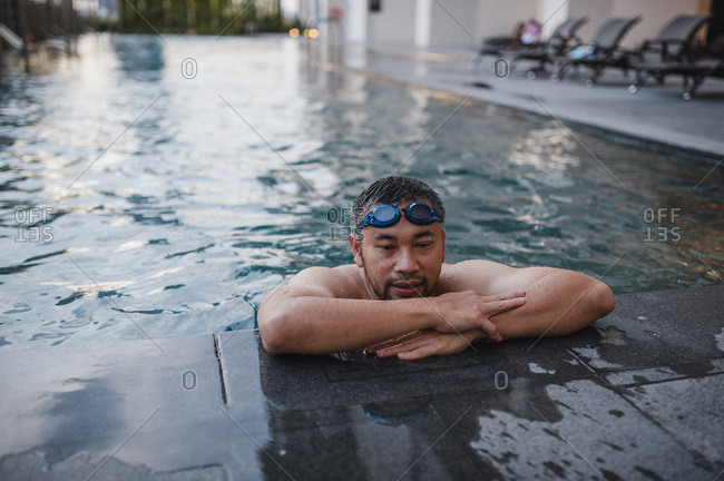 Man on pool ledge wearing goggles