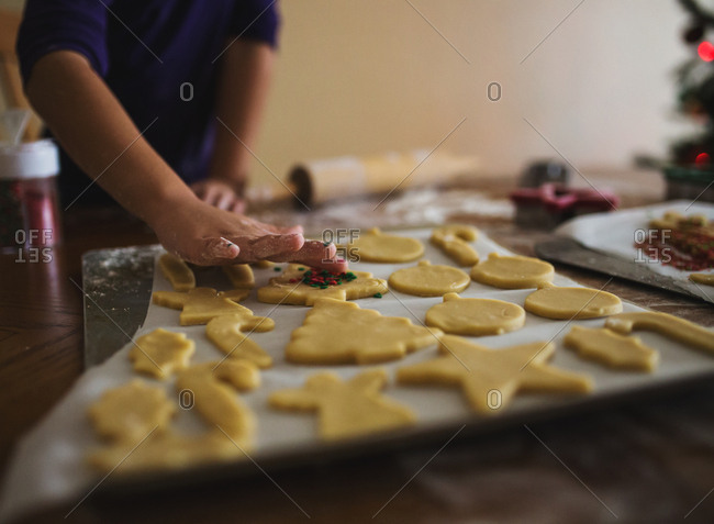 Girl decorating Christmas cut-out sugar cookies