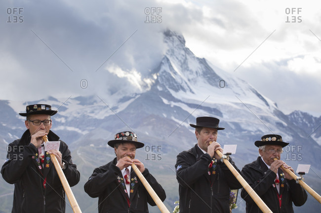 Zermatt, Wallis, Switzerland - August 25, 2014: Four traditionally dressed locals of Zermatt play the Alphorn in front of the Matterhorn mountain. With the passing of time, the alphorn almost totally disappeared as an instrument used by Swiss shepherds. It was only with the romanticism of the 19th century and the revival of folklore and tourism that the alphorn experienced a renaissance and even became a national symbol