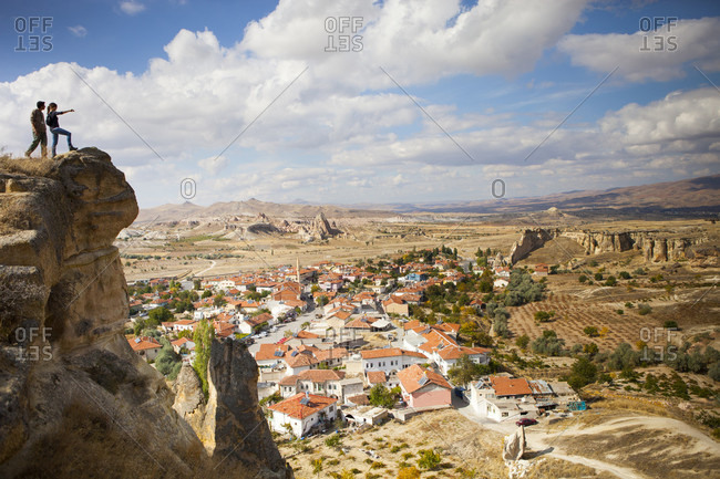 Cappadocia, Turkey - December 12, 2017: Two hikers over looking Cavusin, an old Greek village in Cappadocia Turkey. It has a 5th century church of Saint John, and a marvelous view into the Rose and Red Valleys