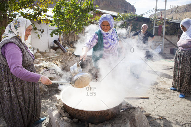 Cappadocia, Turkey - December 12, 2017: Turkish women are making Pekmez on the streets of Cappadocia. Pekmez is a molasses-like syrup obtained after condensing juices of fruit must, especially grape by boiling it. It is used as a syrup or mixed with tahini for breakfast