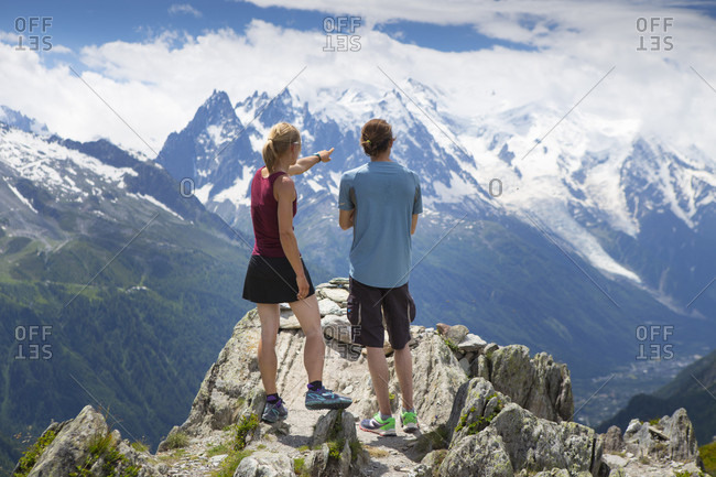 Chamonix, Haute Savoie, France - July 6, 2014: Two runners are standing on top of a mountain, overlooking the Chamonix valley and Mont Blanc range. This region in the French Alps is popular for trail running or sky running