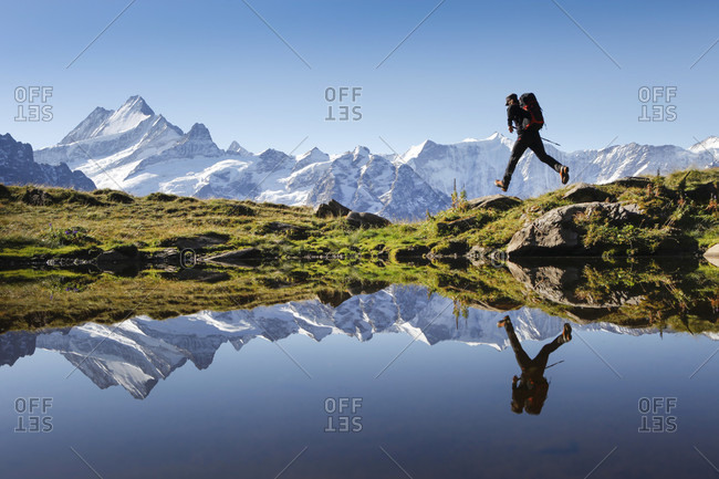 Grindelwald, Bernese Oberland, Switzerland - September 15, 2012: A hiker is jumping while his action posture is being reflected in a mountain lake above Grindelwald in the Swiss Alps. The famous Bernese Oberland peaks are in the background