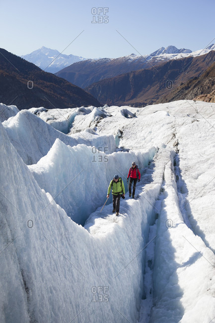 Aletsch, Wallis, Switzerland - December 12, 2017: A mountain guide and his client are walking over an ice ridge of the Swiss Aletsch glacier, one of the largest ice streams in Europe, and the first Unesco World Heritage Site of the Alps. This huge river of ice that stretches over 23 km from its formation in the Jungfrau region (at 4000 m) down to the Massa Gorge in Wallis, around 2500 m below, fascinates and inspires every visitor