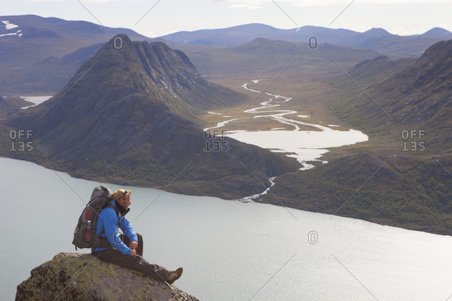 Jotunheimen, Fjord, Norway - September 1, 2012: A hiker is enjoying the view over fjords and mountains while sitting on a rock of the famous Besseggen ridge in Norway. This one day traverse in Jotunheimen National Park is the most popular hike in Norway