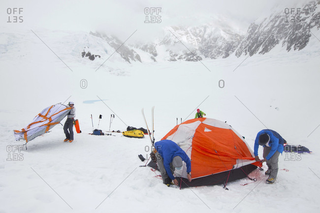 Denali, Alaska, United States - May 31, 2017: Mountaineers are putting up tents in a blizzard on the lower Kahiltna glacier on Denali in Alaska