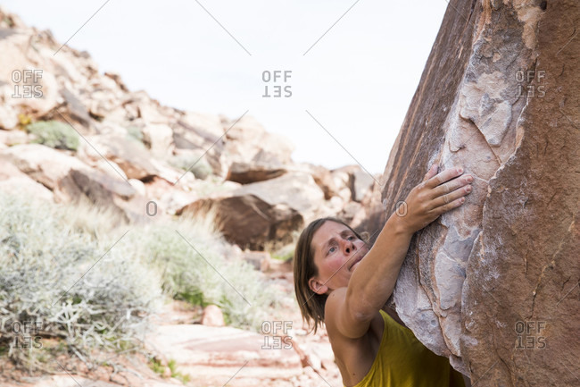 Red Rocks National Park, Nevada, United States - March 4, 2017: A young female tries hard on a boulder in Red Rocks National Park, Nevada