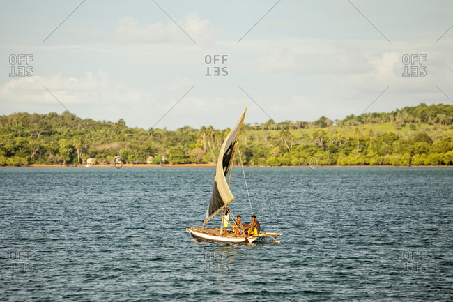 Dumaga Bay, Milne Bay, Papua New Guinea - July 5, 2009: Men sailing on a small boat in Louisiade Archipelago, a string of ten larger volcanic islands frequently fringed by coral reefs