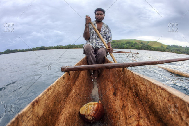 Nimoa Island, Milne Bay, Papua New Guinea - July 7, 2009: Man paddling on outrigger canoe