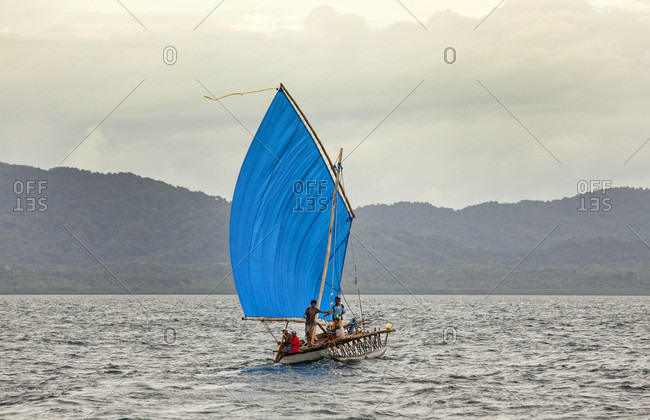 Nimoa Island, Milne Bay, Papua New Guinea - July 6, 2009: Sailboat with blue sail sailing in water