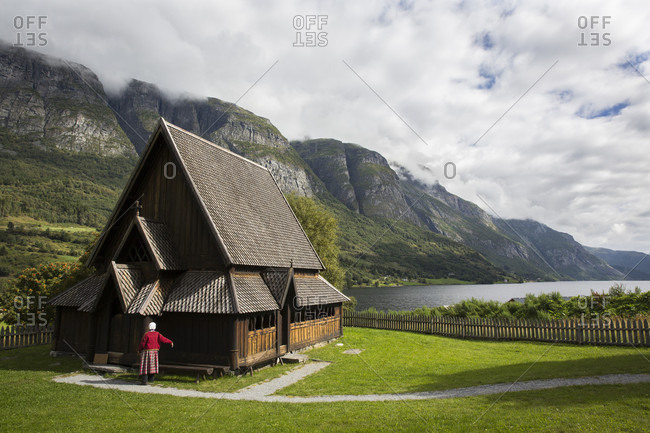 Oye, Norway - August 18, 2016: Photograph of woman tending to the stave church