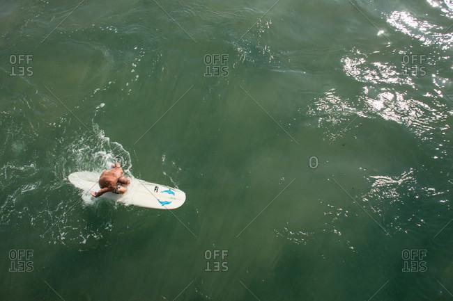 Durban, KwaZulu-Natal, South Africa - May 26, 2014: Senior man paddling surfboard next to pier near promenade on Golden Mile