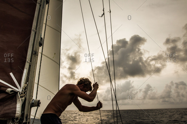 Caribbean Sea, Honduras - June 2, 2013: Shirtless man adjusting sails while sailing