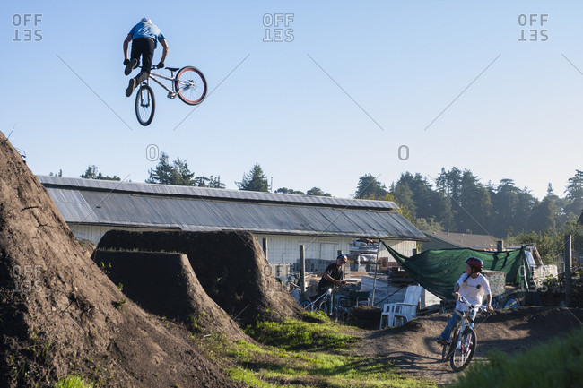 Aptos , CA, USA - October 22, 2009: Jack Fogelquist does a Tail Whip while his fellow riders look on