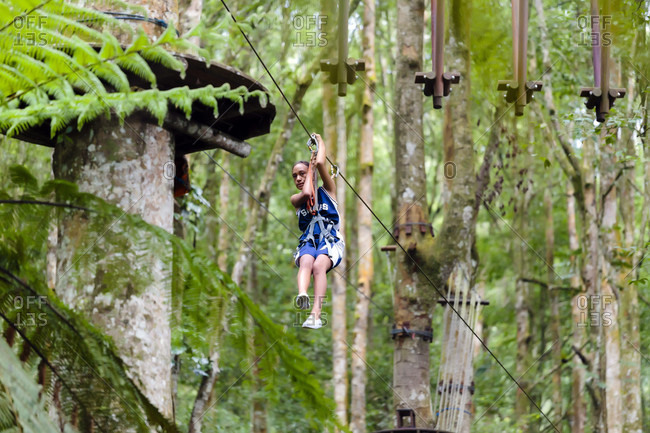 Kintamani, Bali, Indonesia - May 9, 2017: A girl descends a zip line at a Treetop Adventure Park