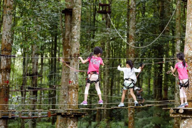 Kintamani, Bali, Indonesia - May 9, 2017: Three girls climb across a taut line at a Treetop Adventure Park