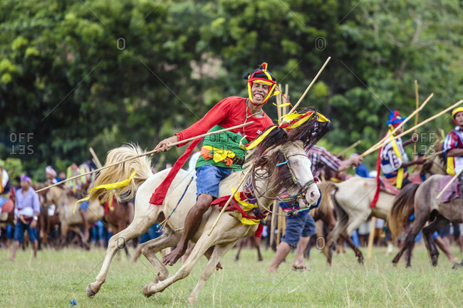 Sumba, Indonesia - December 12, 2017: Man riding horse with spear and competing at Pasola Festival