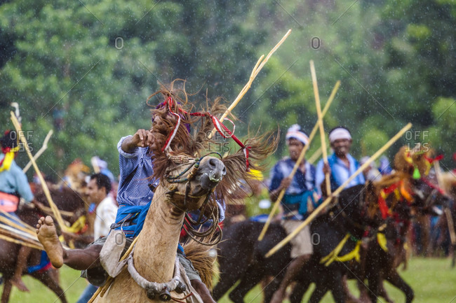 Sumba, Indonesia - December 12, 2017: Group of men riding horses and competing in Pasola Festival