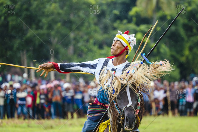 Sumba, Indonesia - December 12, 2017: Man throwing spear and riding horse at Pasola Festival