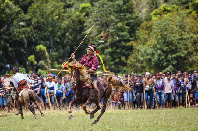 Sumba, Indonesia - December 12, 2017: Men on horses competing in Pasola Festival