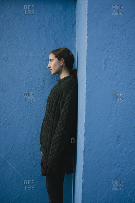 Portrait of teenage girl with brown hair in ponytail wearing black knitted jumper, leaning against blue wall.