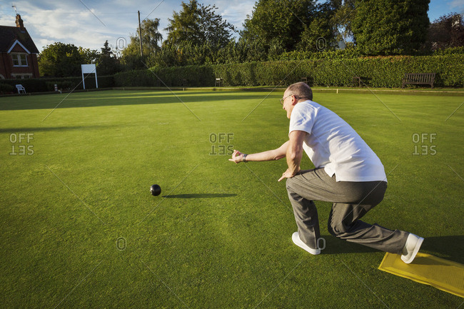 A lawn bowls player standing on a small yellow mat preparing to deliver a bowl down the green, the smooth grass playing surface.