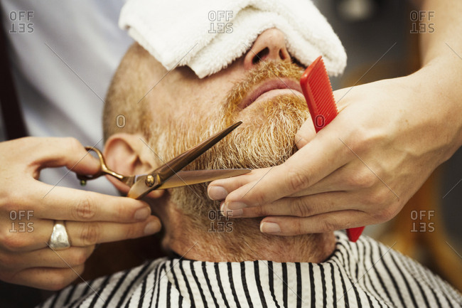 A customer sitting in the barber's chair, with a hot towel on his face, and a barber trimming his beard.