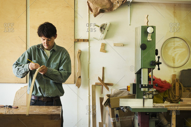A craftsman marking a piece of curved wood with a pencil.