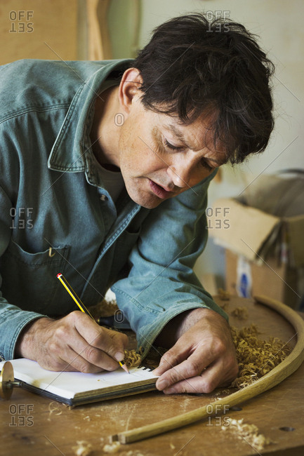 A craftsman using pencil and paper to do calculations and measurements on a workbench, among the wood shavings.