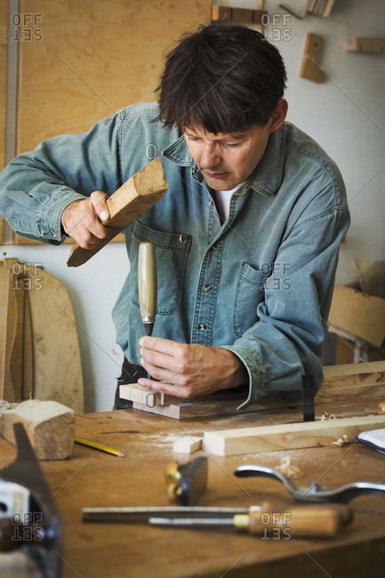A craftsman using a piece of wood on the end of a chisel to mark a piece of wood.
