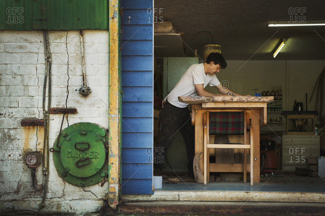 A craftsman working in his workshop, using tools on a block of wood.