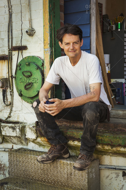 A man in a teeshirt having a tea break, sitting on the steps of a workshop.