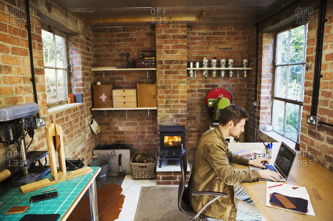 A designer seated in his leatherwork workshop, at a desk using a laptop. Woodburning stove with a glowing fire lit.