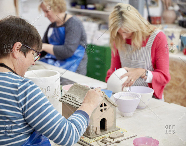 A group of people seated at a workbench in a pottery studio, decorating and shaping clay objects.