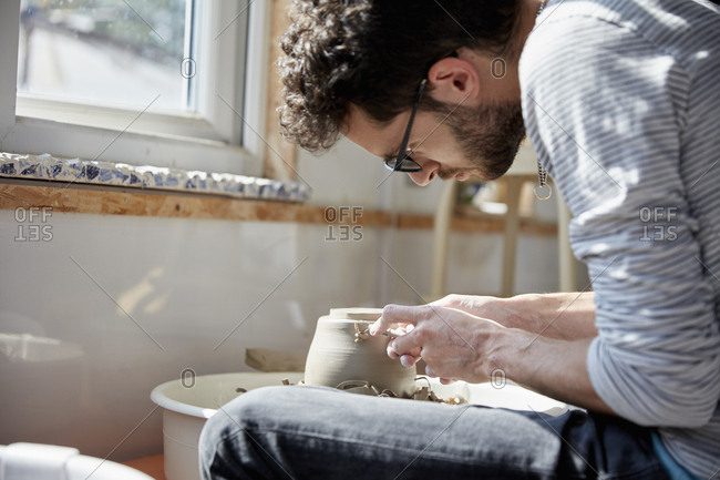 Man seated at a potter's wheel, molding the wet clay on the spinning turntable, in a pottery studio