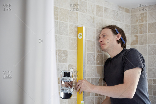 A builder using a spirit level to check his work on a wall of tiles, refurbishing a bathroom.