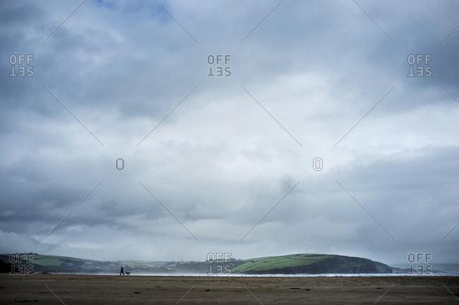 Silhouette of a dog walker and dog on a sandy beach under an overcast sky. Headland and coastline.